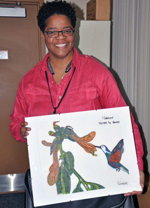 Yvettea Johnson, proudly displays her painting. This piece was on display at University Hospitals in February.